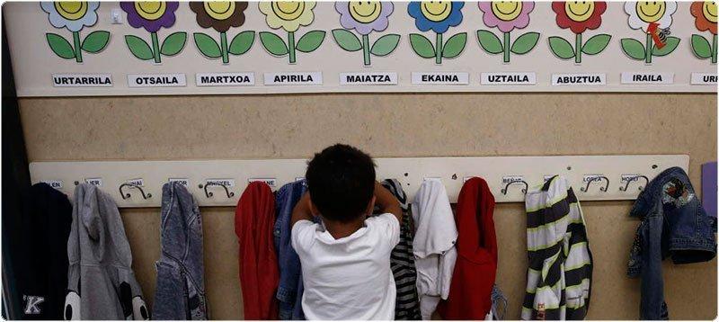 Un niño coloca su prenda de vestir en un aula de un colegio público. (EFE/Jesús Diges)