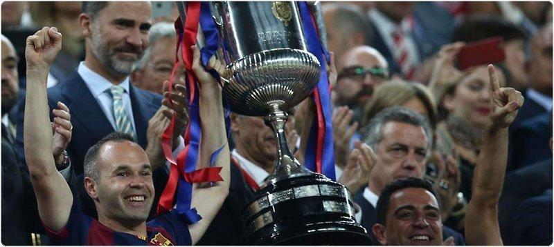 Los jugadores del FC Barcelona Iniesta y Xavi levantan el trofeo de la Copa del Rey. (EFE)