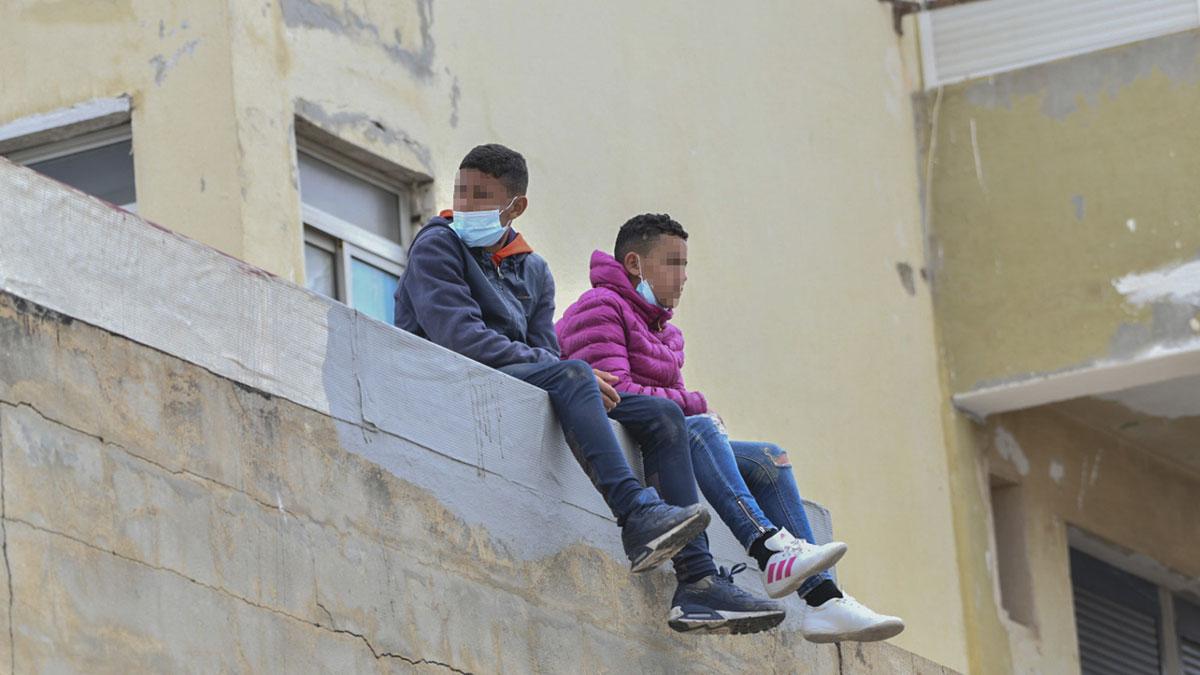 Dos niños marroquíes sobre un muro en la nave de primera acogida del polígono del Tarajal. Europa Press